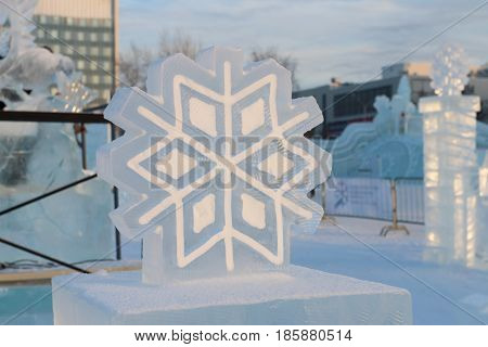Big man-made ice and snowy snowflake in ice town at winter evening