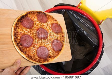 Close-up Of A Person Throwing Salami Pizza On Chopping Board In Dustbin