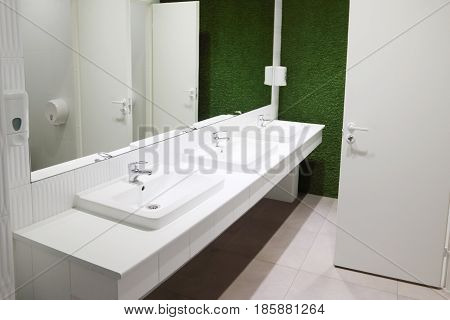 Three white sinks in toilet with big mirror and green lawn wall