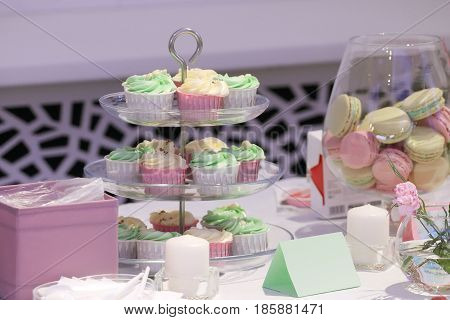 Sweet cupcakes and macarons are on table during celebration