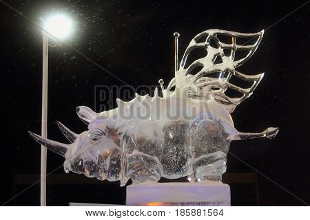 PERM RUSSIA - FEB 1 2017: Sculpture Flying rhinoceros at night Ice town of Perm in 2017 Ekosad - largest in Russia