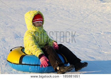 Girl sits on snowtube and looks away at sunny and frosty winter day