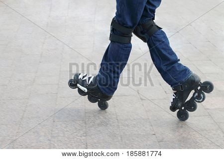 Young man wearing roller skates and protective knee pads riding on a city tile
