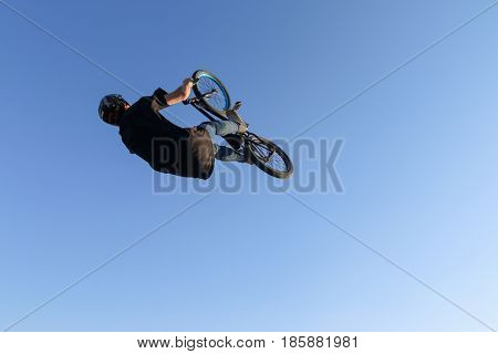 Extreme biker black t-shirt blue jeans and a helmet doing a somersault in aeromat