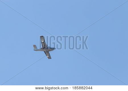 White passenger plane flies highly in the sky on a bright Sunny day without clouds