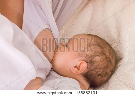 The little child sucks his mother's breast on a bed with white satin covers