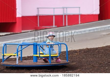 Little girl in denim overalls and a cute hat riding on a carousel in the yard on a warm Sunny day