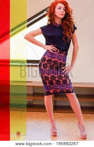 Beautiful young woman with red curly hair standing in a dressing room near the color of the walls