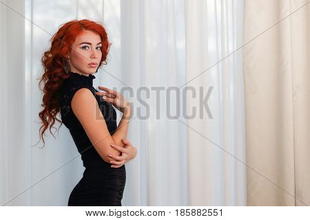 Graceful young woman in short black dress standing near window with white curtains