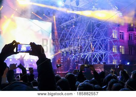 Male hand shoots video by smartphone during concert with laser show at night