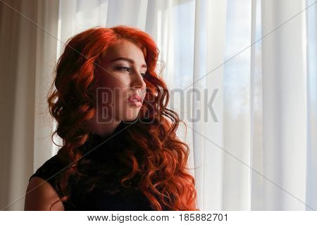 Young woman with beautiful curly hair standing at the window and gently looking forward