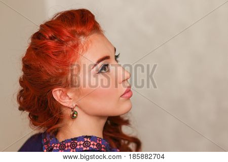 Pretty girl with subtle makeup and red hair in braided hairstyle in profile
