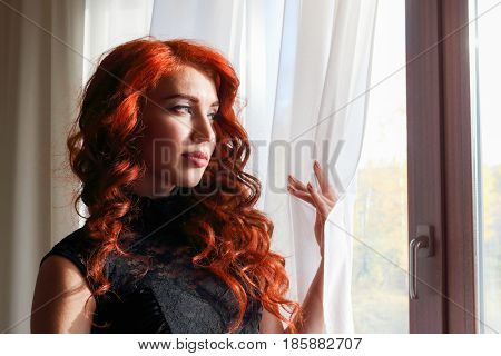 Cute red-haired girl in a beautiful lace black dress standing at the window and looks into the distance