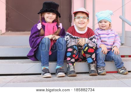 Three little children in bright clothes sitting on the stairs at the entrance