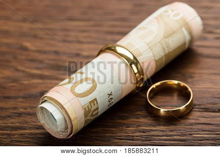 Golden Wedding Rings With Rolled Up Euro Notes On Wooden Table