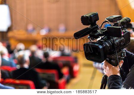 Closeup of a Video Camera Filming a Seminar / Meeting / Conference