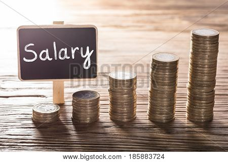 Close-up Of Salary Text On Small Chalk Board With Increasing Coin Stack On Wooden Table