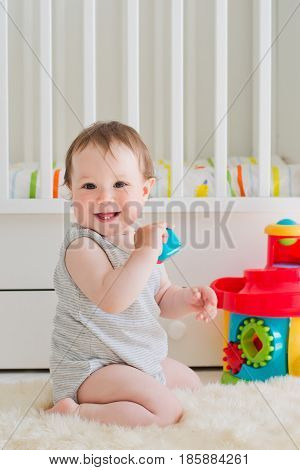 baby girl playing with educational toy in nursery. Vertically
