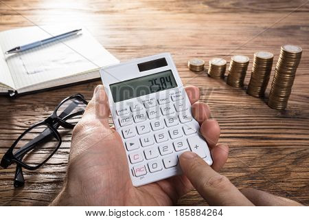 Close-up Of A Person Calculating Profit On Calculator With Notebook Eyeglasses And Coin Stacked