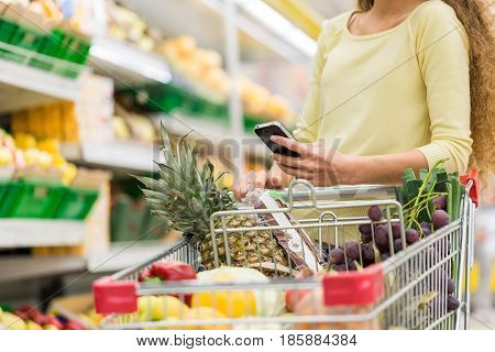 Customer Pushing a Shopping Cart Full of Groceries and Using Smartphone