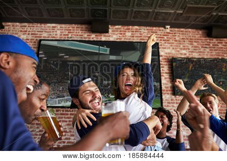 Friends Watching Game In Sports Bar On Screens Celebrating