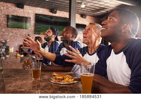 Male Friends At Counter In Sports Bar Watching Game