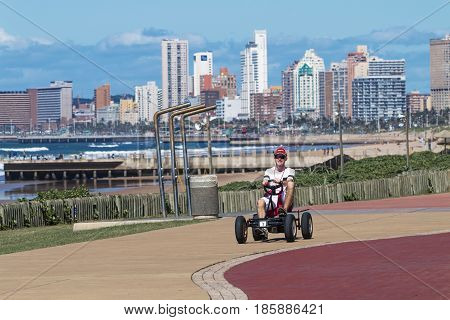 Man Riding Peddle Car On Beachfront Promenade