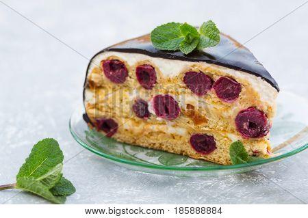Cake with cherry, cream and chocolate icing