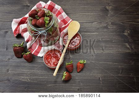 Large glass jar full of fresh strawberries with towel on a dark wooden table and a large wooden spoon for jam, homemade jam concept
