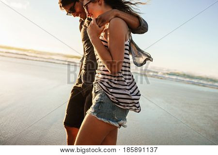 Couple Strolling Together On Beach On A Summer Day