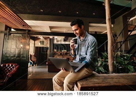 Shot of young man sitting relaxed looking at laptop and having coffee. Male executive using laptop during coffee break.
