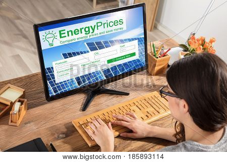Close-up Of A Woman Comparing The Energy Prices On Computer At Office Desk