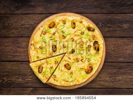Seafood pizza with mussels top view on wood, thin pastry crust with slice cut, fast food delivery