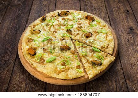 Italian seafood pizza with mussels on wood, thin pastry crust with slice cut, fast food delivery
