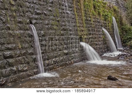 Square concrete blocks dam on the river with holes for drain water