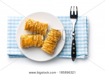 Sweet dessert baklava on napkin with fork. Isolated on white background. Top view.