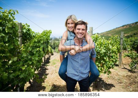 Portrait of smiling young couple piggybacking at vineyard against blue sky