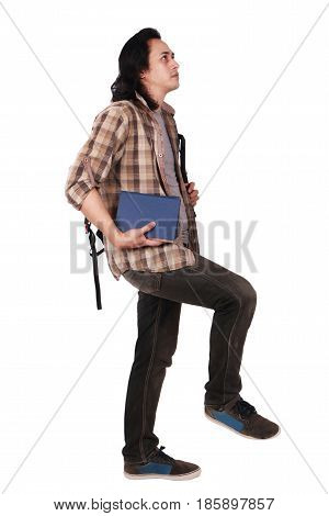 Photo image portrait of a cute young Asian male student with long hair looking up and stepping forward while holding books isolated on white
