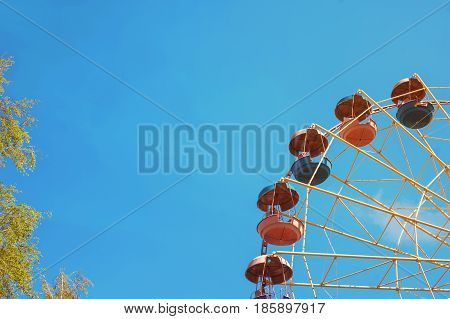 Cabins the ferris wheel against the blue sky. Summer fun at the amusement Park.