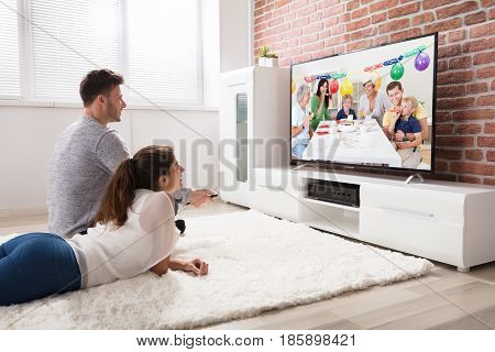 Young Couple Watching Party Celebration Video On Television At Home