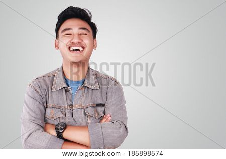 Photo image portrait of a cute young successful Asian male student laughing and standing with arms crossed in front of his chest