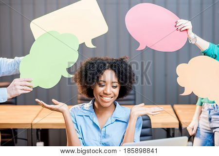 Portrait of creative african ethnicity businesswoman sitting with thought bubbles at the office