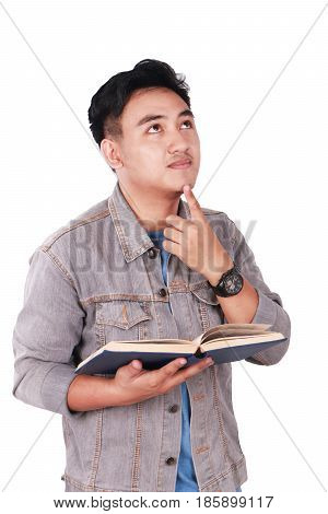 Photo image portrait of a cute young Asian male student standing looking up and thinking while reading a book isolated on white