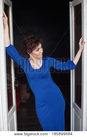 woman in blue evening gown stands against the wall