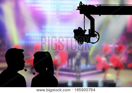 Silhouette image of the female director and cameraman or photographer talking or consulting to working with hanging cemara on crane on blurry concert on stage background in television studio