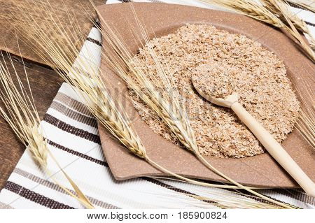 Bamboo plate and wooden spoon filled with wheat bran surrounded by wheat ears