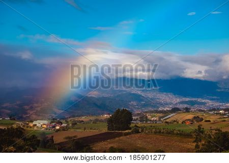 Green meadows and rainbow. View from slope of volcano of Irazu to the valley. Costa Rica