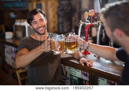 Smiling man toasting beer mug with male friend in bar