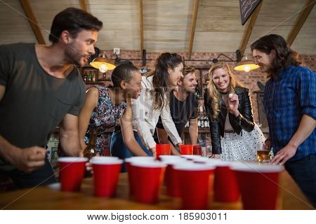 Happy friends playing beer pong game on table in bar