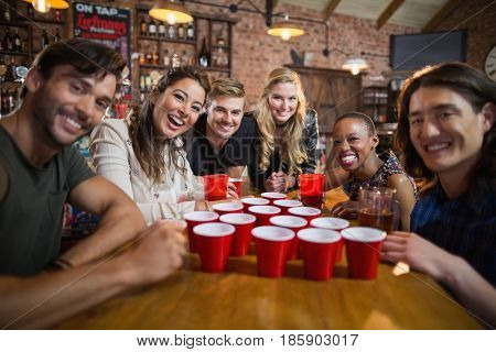 Portrait of smiling friends around disposable cups on table in bar